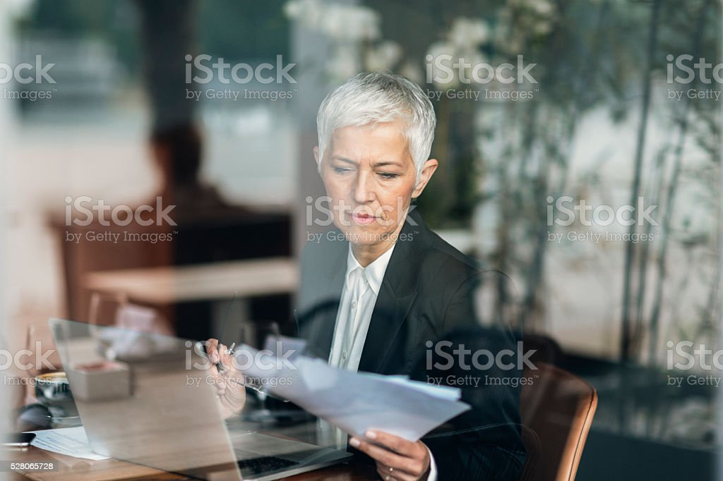 Mature businesswoman Working On Her Laptop. stock photo