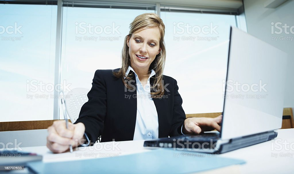 Mature businesswoman writing notes while using laptop royalty-free stock photo