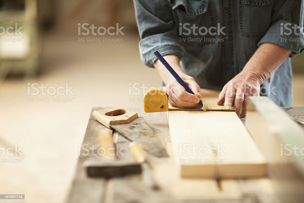 Mature caprenter measuring a wooden plank stock photo