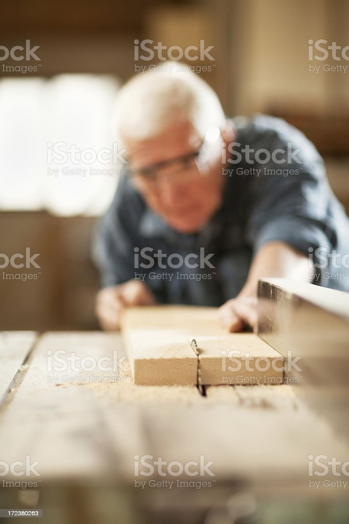 Mature carpenter cutting wooden plank royalty-free stock photo