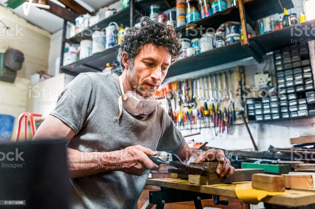 Mature carpenter hammering on timber in workshop stock photo