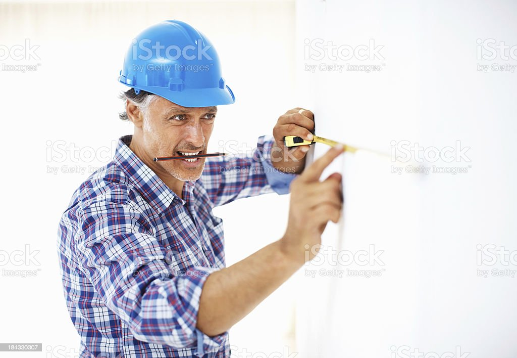 Mature carpenter measuring wall royalty-free stock photo