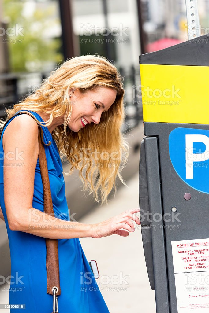Mature caucasian blond woman paying for parking stock photo