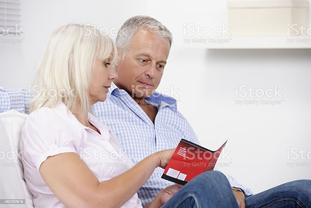 Mature Caucasian Couple Looking At A Brochure stock photo