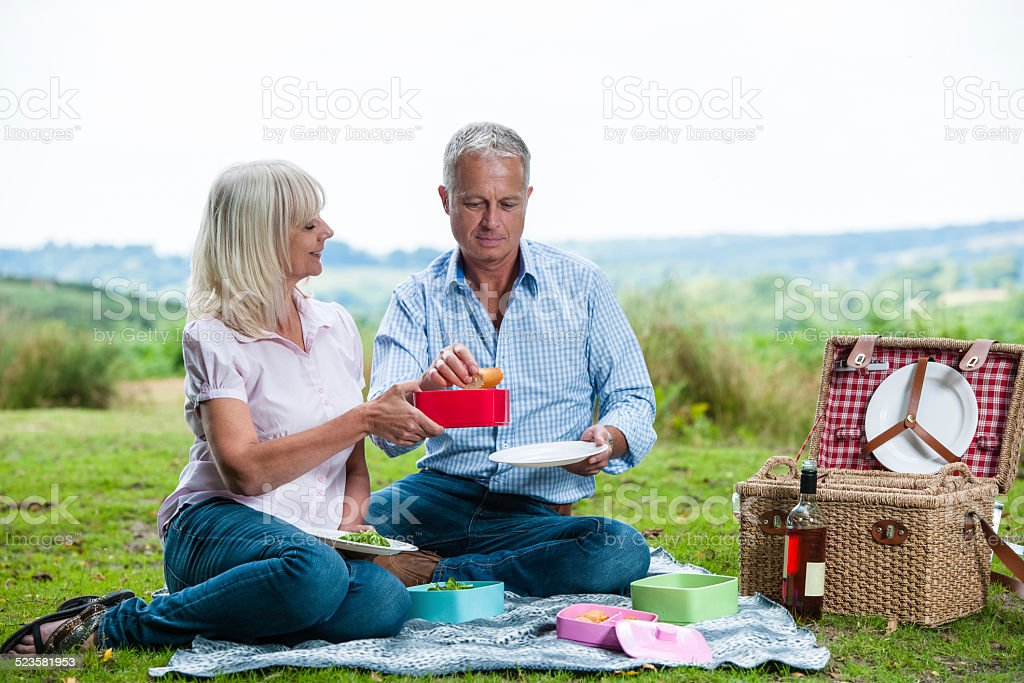 Mature Caucasian Couple Sharing A Picnic stock photo