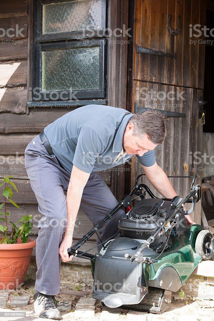 Mature Caucasian Man Moving a Lawn Mower stock photo