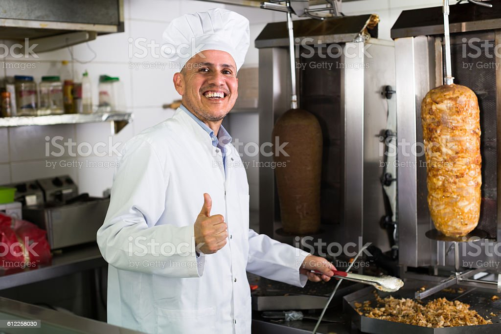 mature chef holding thumbs up on kitchen stock photo