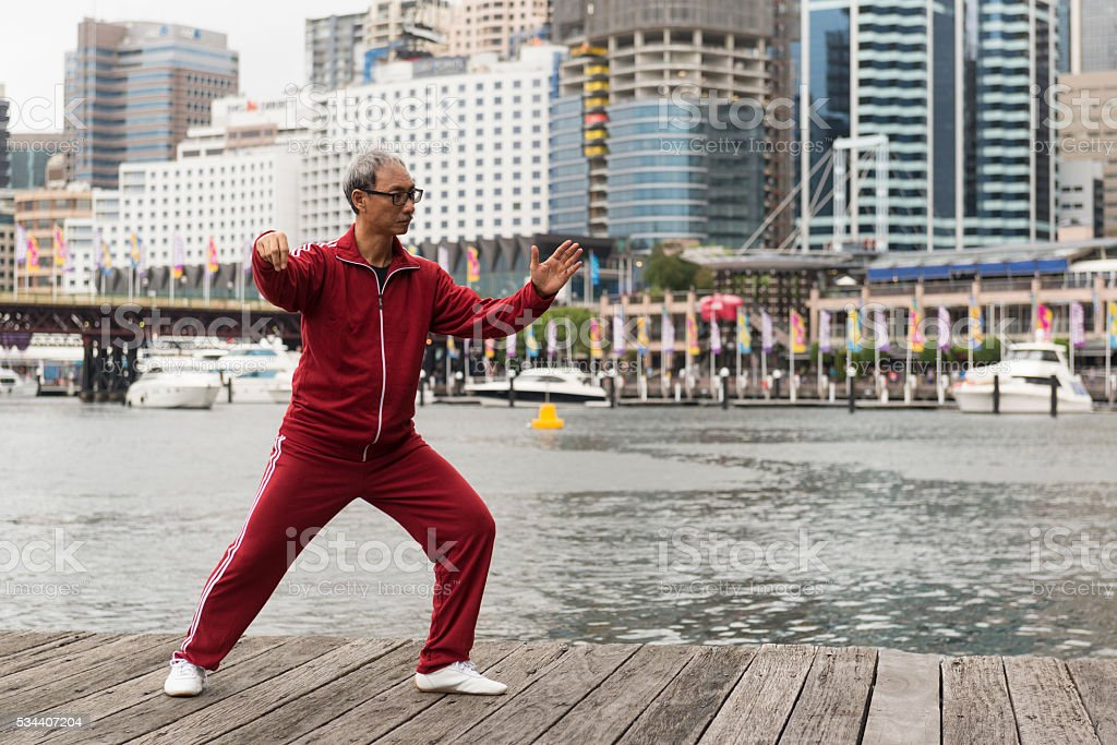 Mature Chinese Man Practising Tai Chi Chuan on Quay Side stock photo