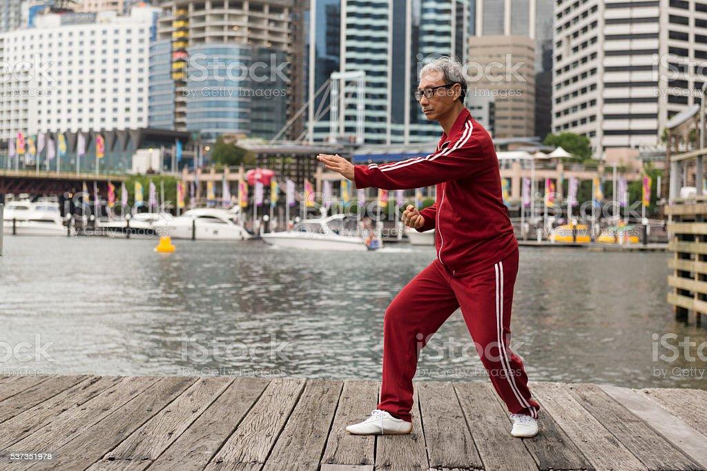 Mature Chinese Man Practising Tai Chi Chuan on Quay Side stock photo