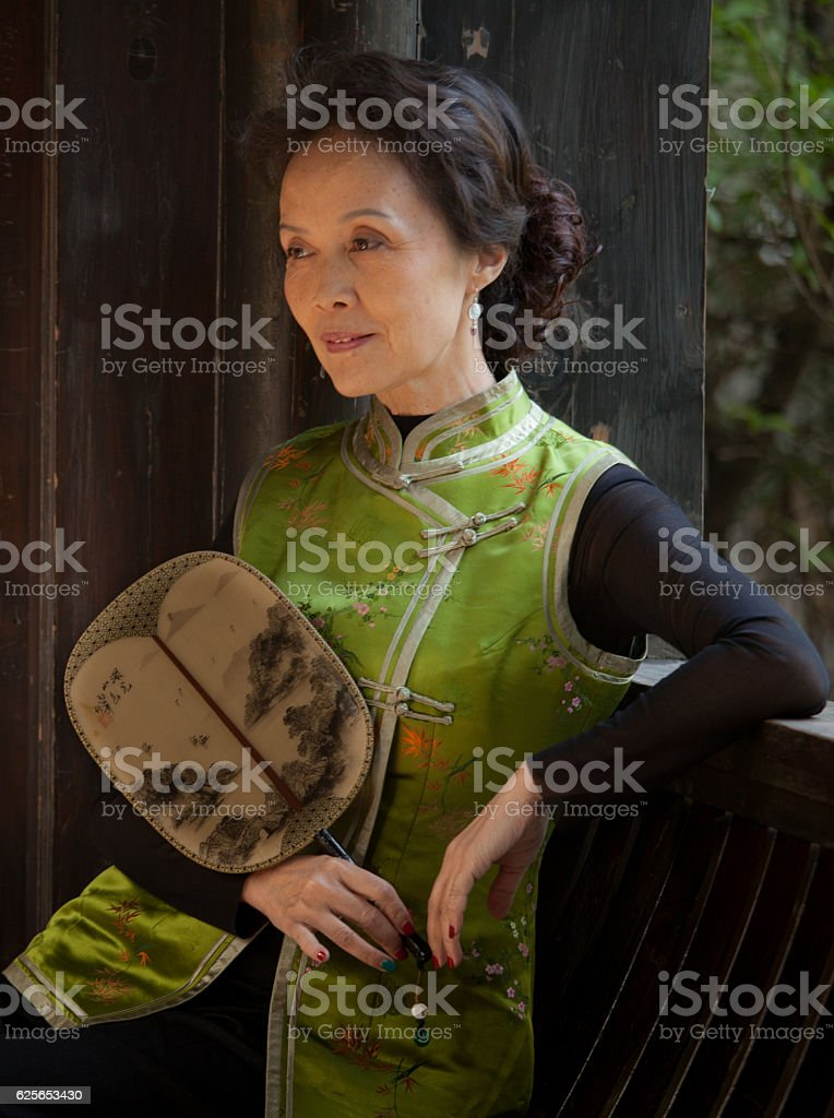 Mature Chinese woman in traditional attire holding old-fashioned fan stock photo