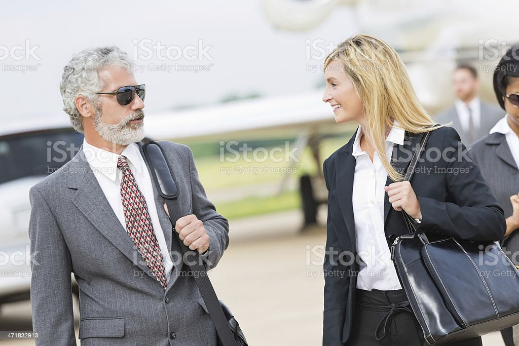 Mature colleagues talking after deboarding company's private jet royalty-free stock photo