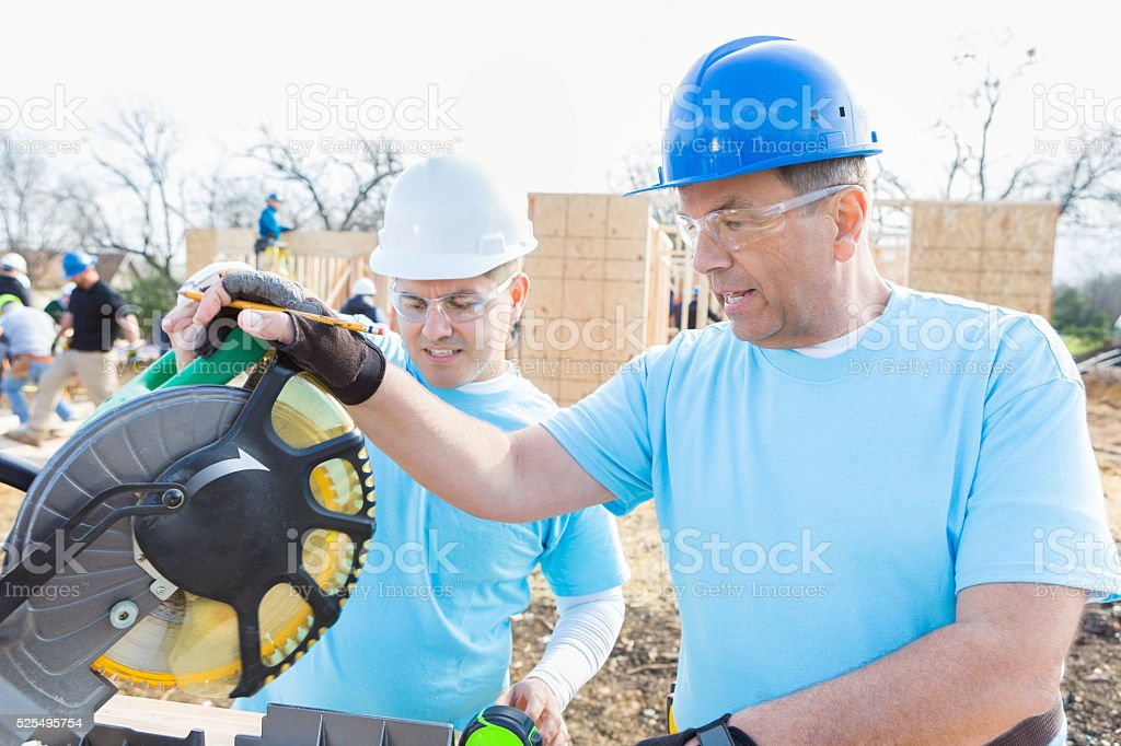 Mature construction worker uses saw at work site stock photo