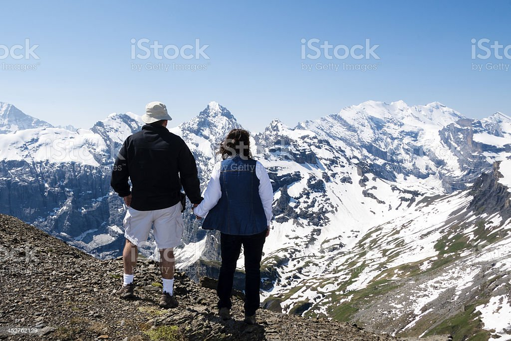 Mature couple admiring a snow covered mountain range royalty-free stock photo