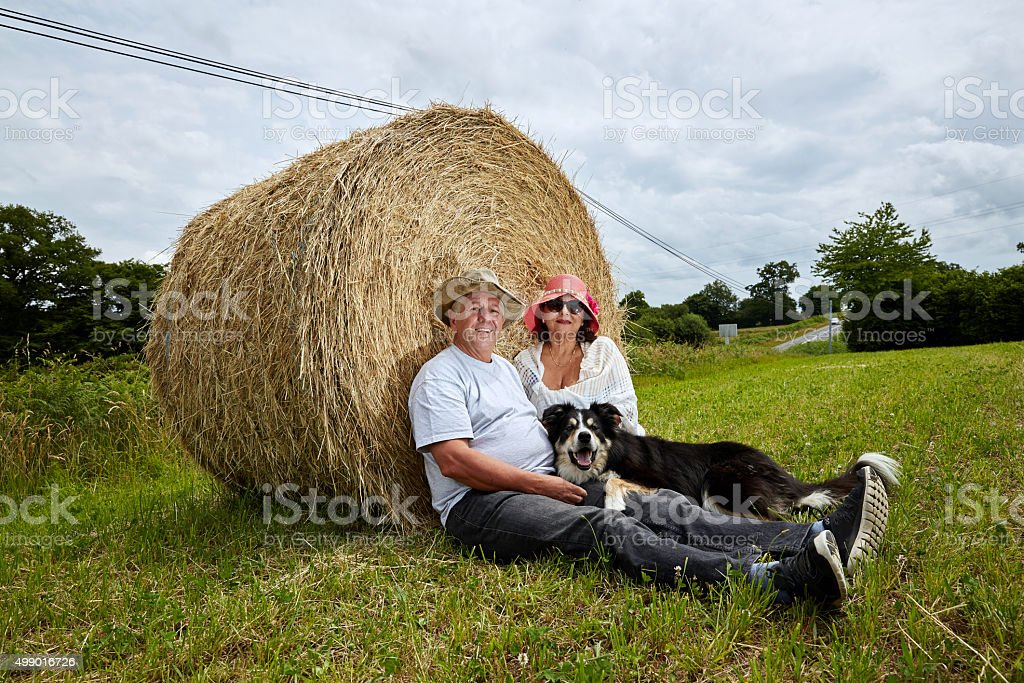 Mature couple and dog relaxing on hay bale stock photo