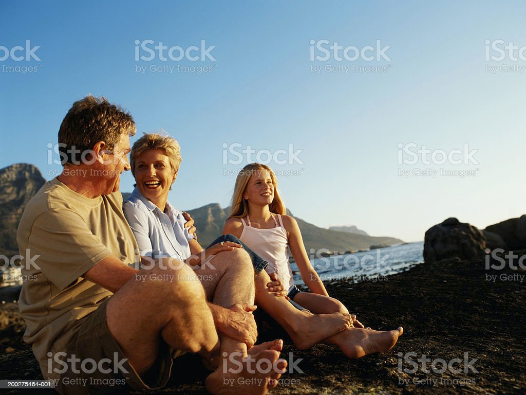 Mature couple and girl (10-12) sitting by lake royalty-free stock photo