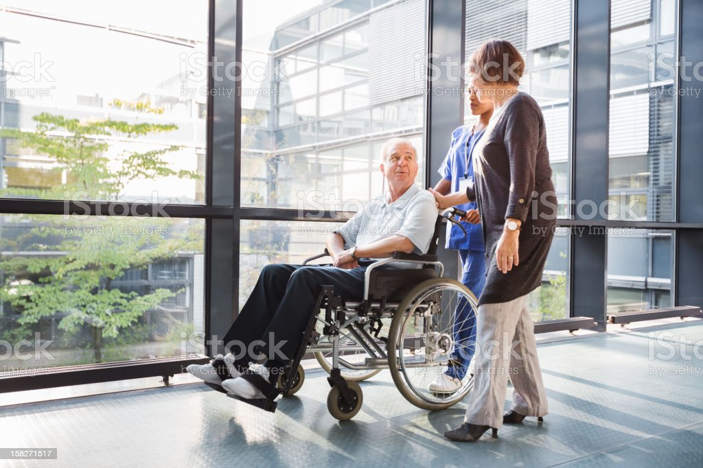 Mature Couple and Nurse in Hallway stock photo