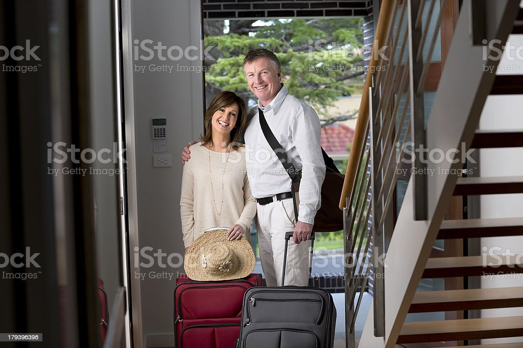 Mature couple arriving home from a vacation royalty-free stock photo