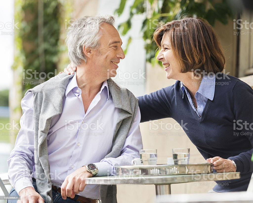 Mature Couple at cafe table and smiling stock photo