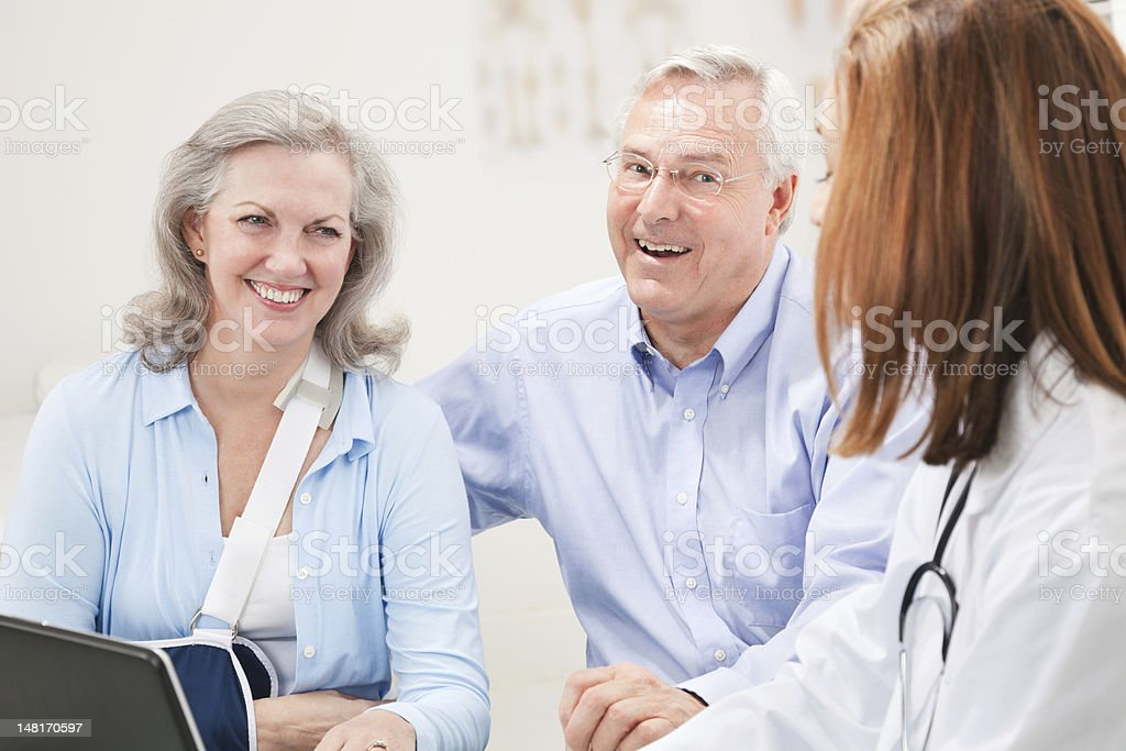 Mature Couple at Doctor's Office Talking to Doctor royalty-free stock photo