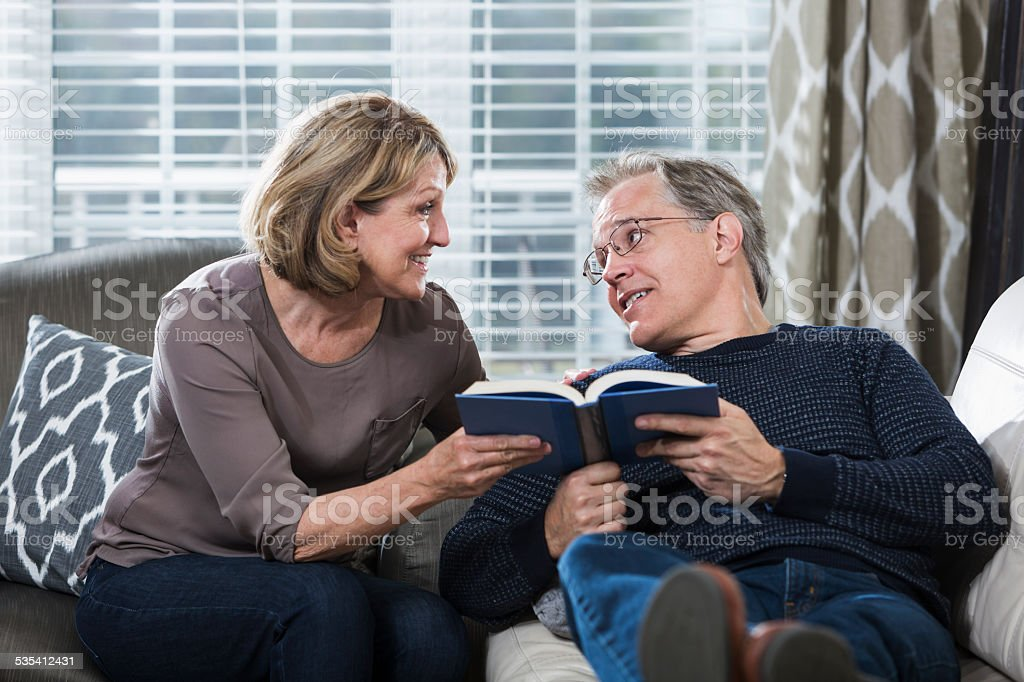 Mature couple at home reading book stock photo