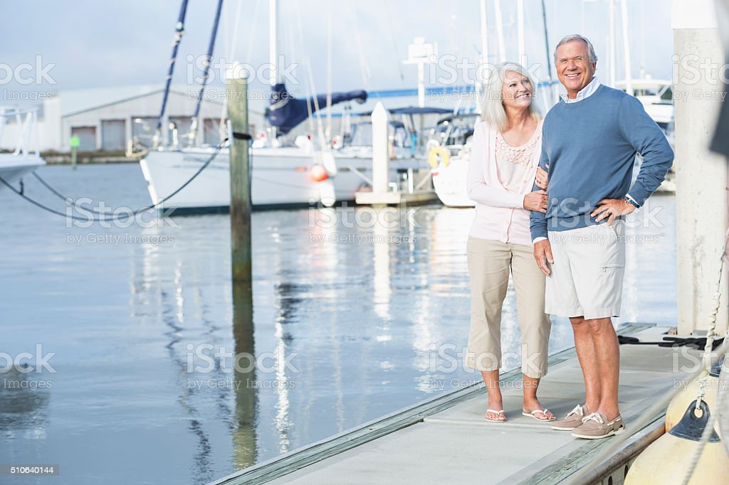 Mature couple at marina standing on dock stock photo