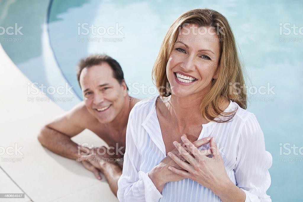 Mature couple at swimming pool stock photo