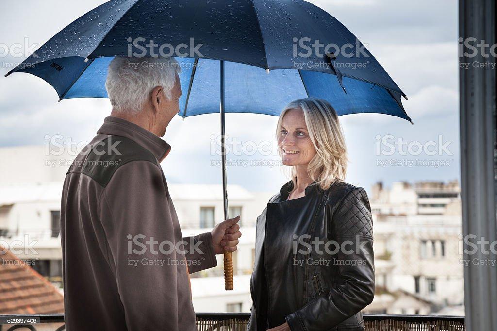 mature couple brave rain on balcony of apartment in Paris stock photo