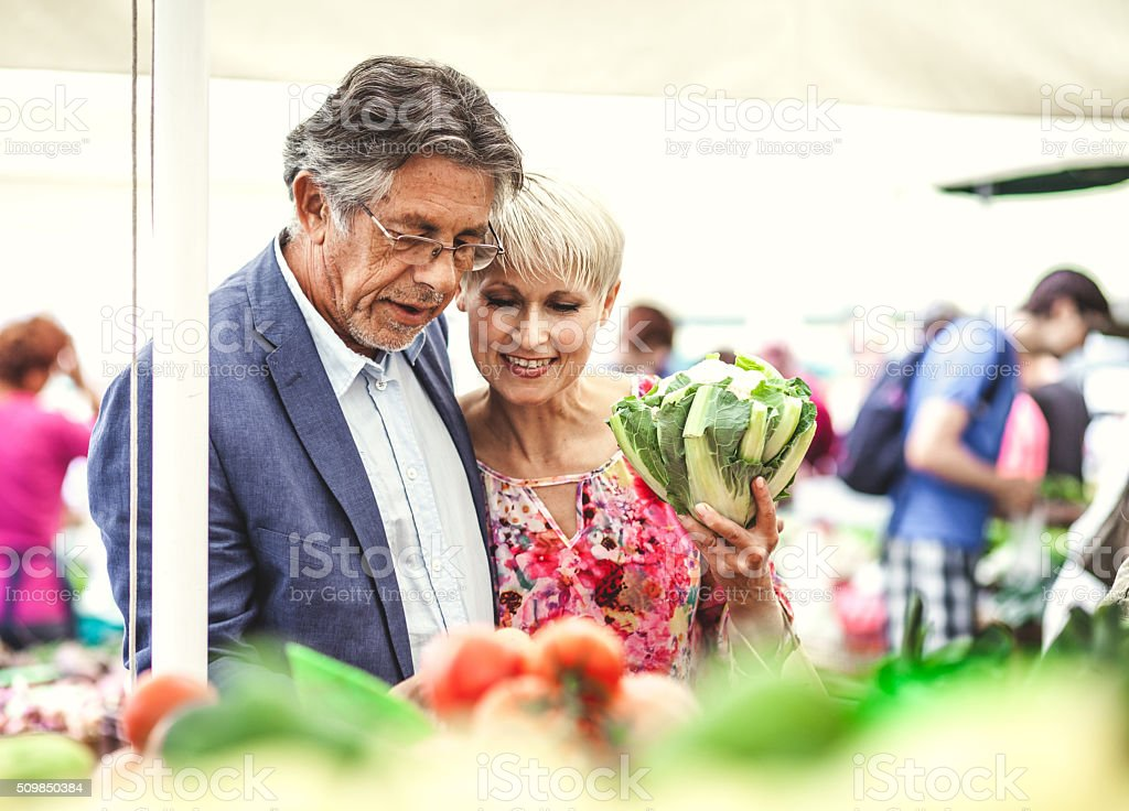 Mature couple buying food on the street market stock photo