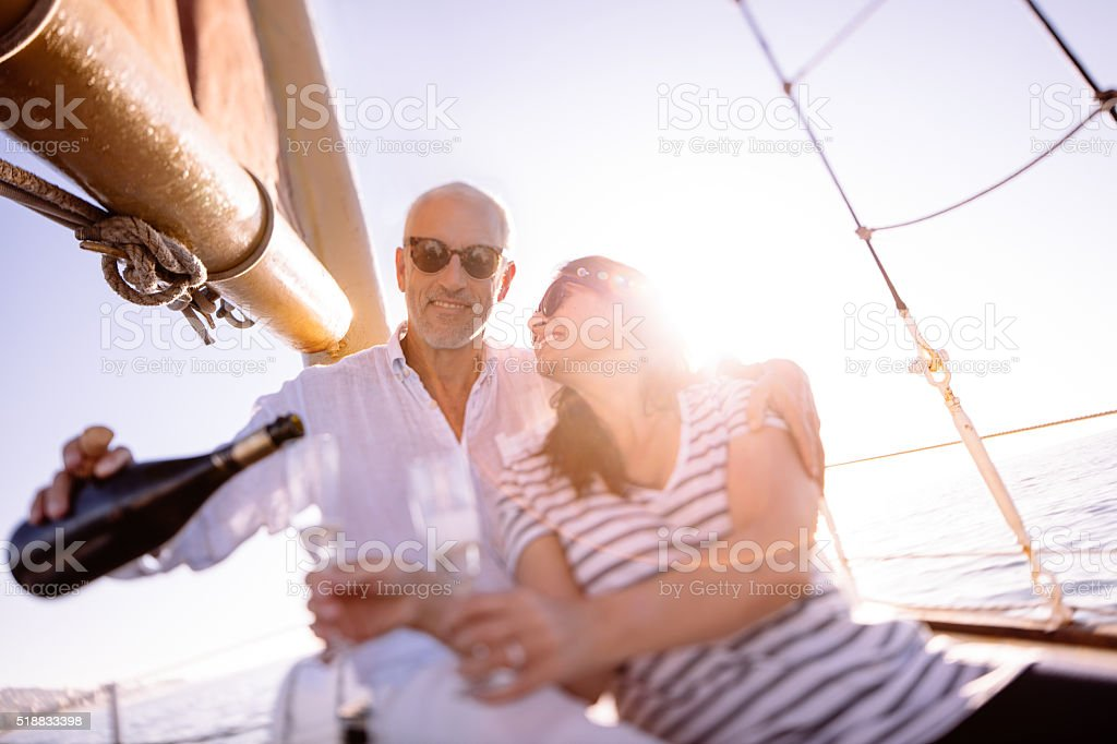 Mature couple celebrating with champagne on a sunset yacht cruis stock photo