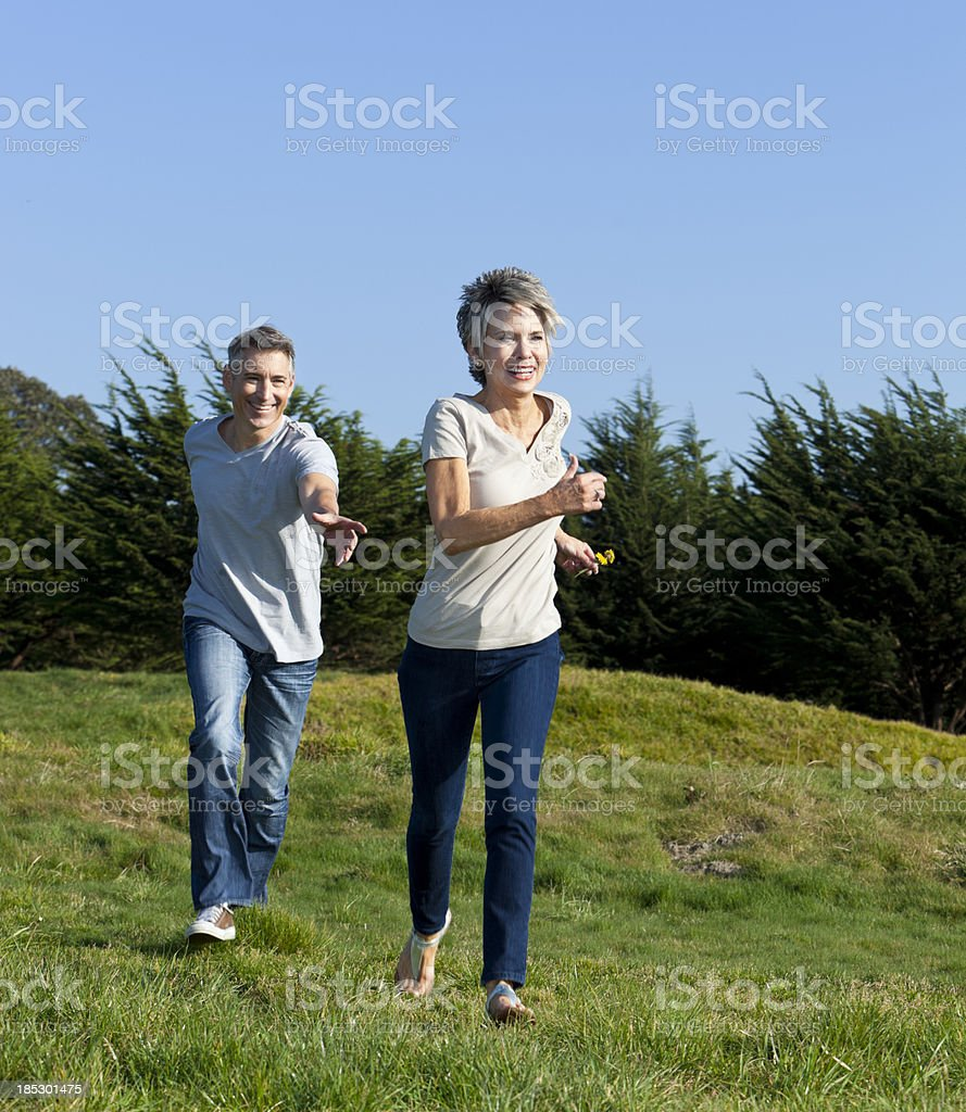 mature couple chasing one another stock photo