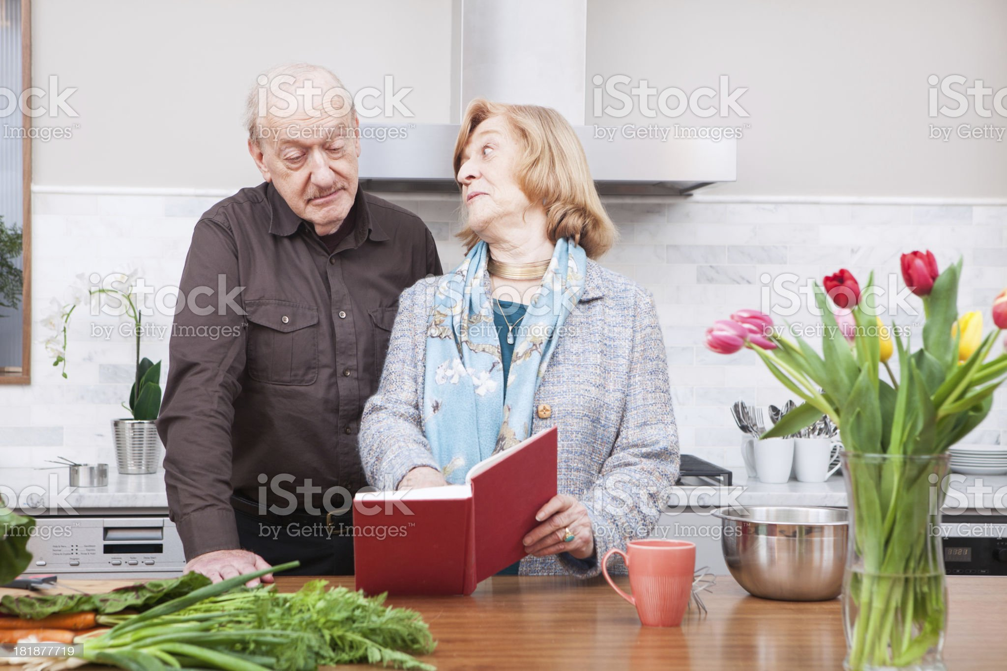 Mature couple choosing recipe from cookbook in kitchen royalty-free stock photo