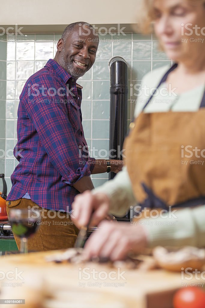 Mature couple cooking in country kitchen stock photo