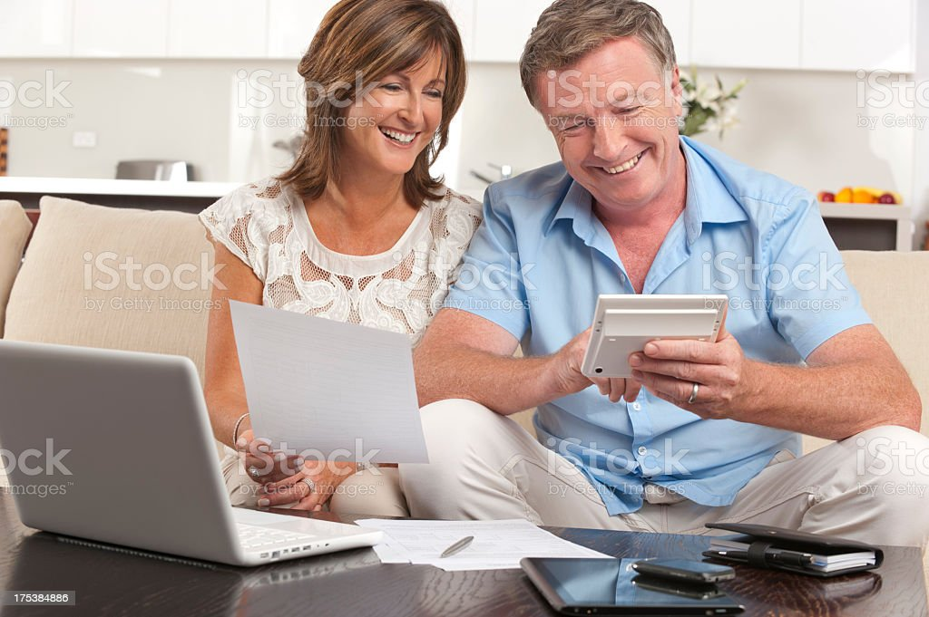 Mature couple doing paperwork with a calculator royalty-free stock photo
