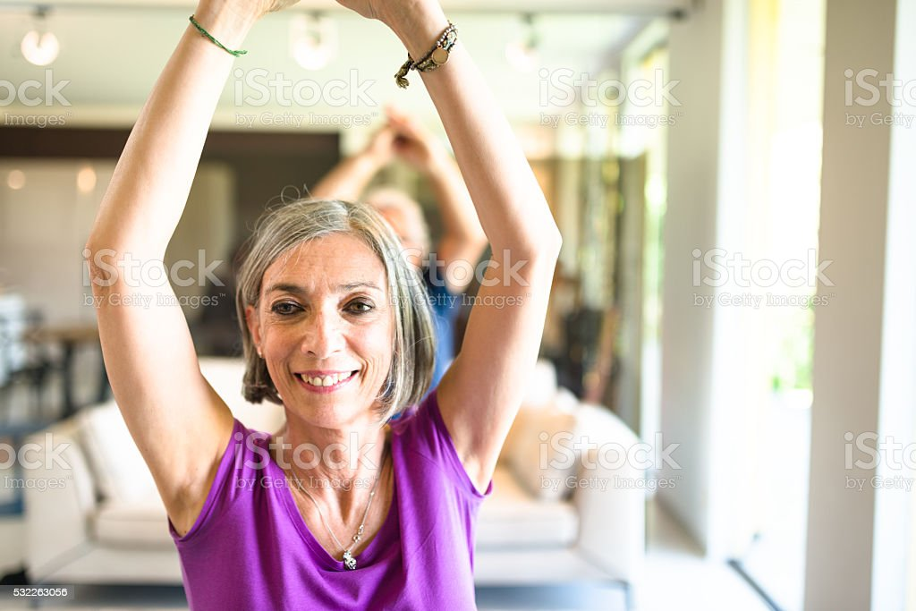 mature couple doing pilates and yoga at home stock photo