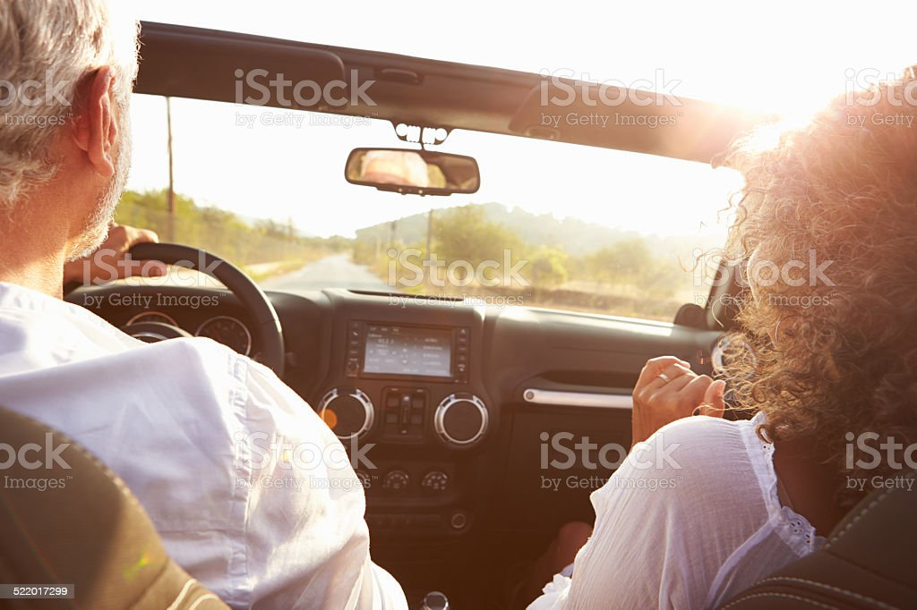 Mature Couple Driving Along Country Road In Open Top Car stock photo