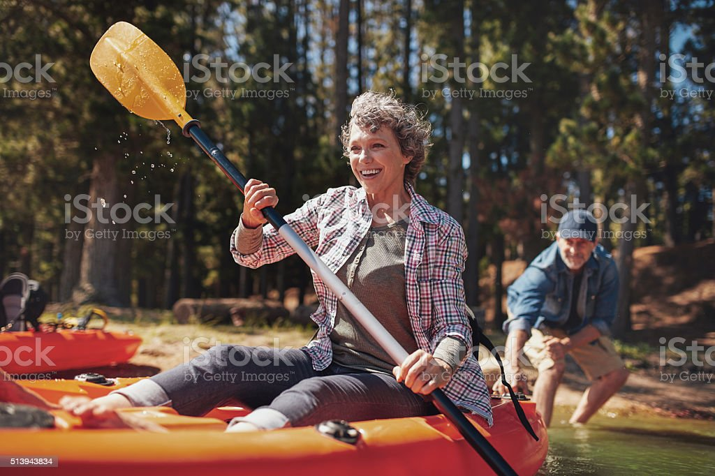Mature couple enjoying a day at the lake with kayaking stock photo