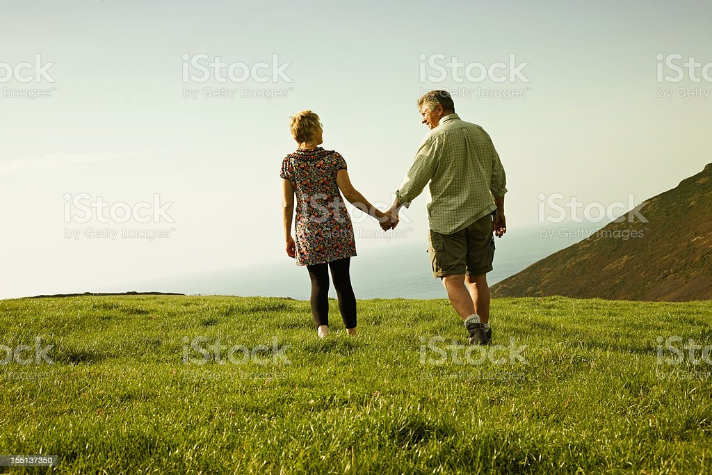 Mature couple enjoying autumn walk on coastal path stock photo