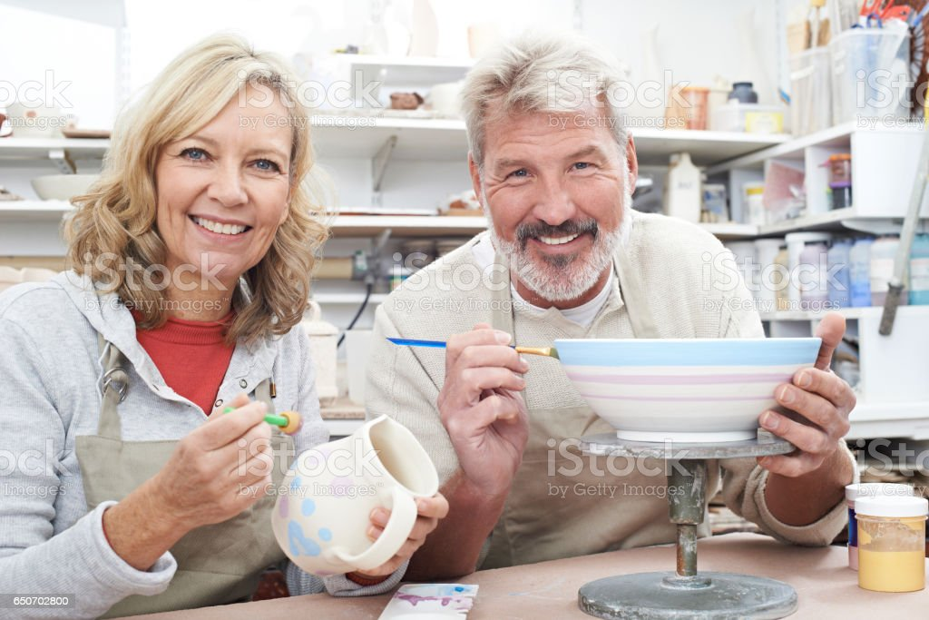 Mature Couple Enjoying Pottery Class Together stock photo