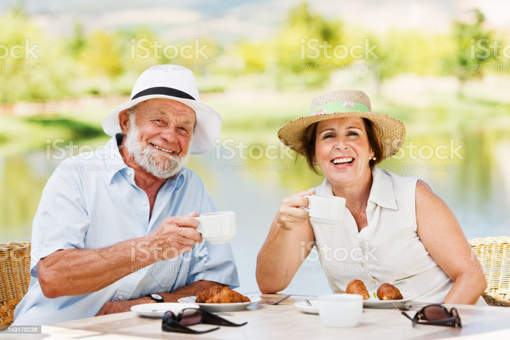 Mature couple enjoying tea on a lakeside terrace stock photo