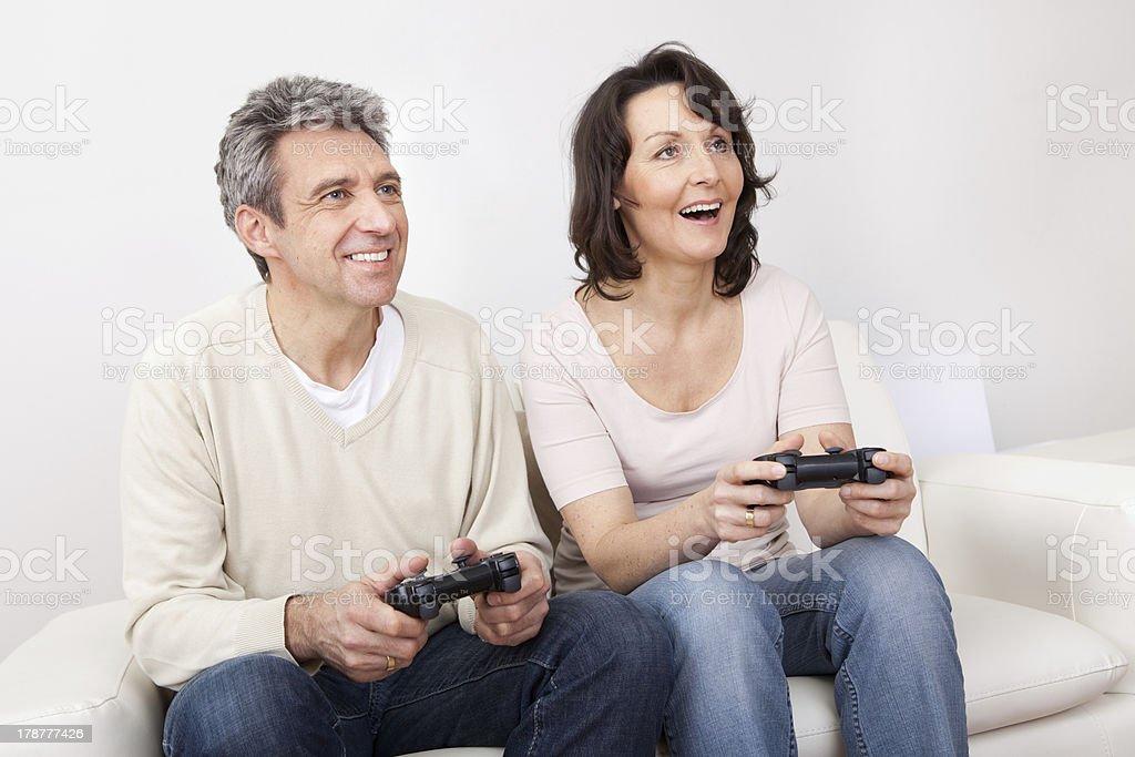 Mature couple enjoying videogames royalty-free stock photo