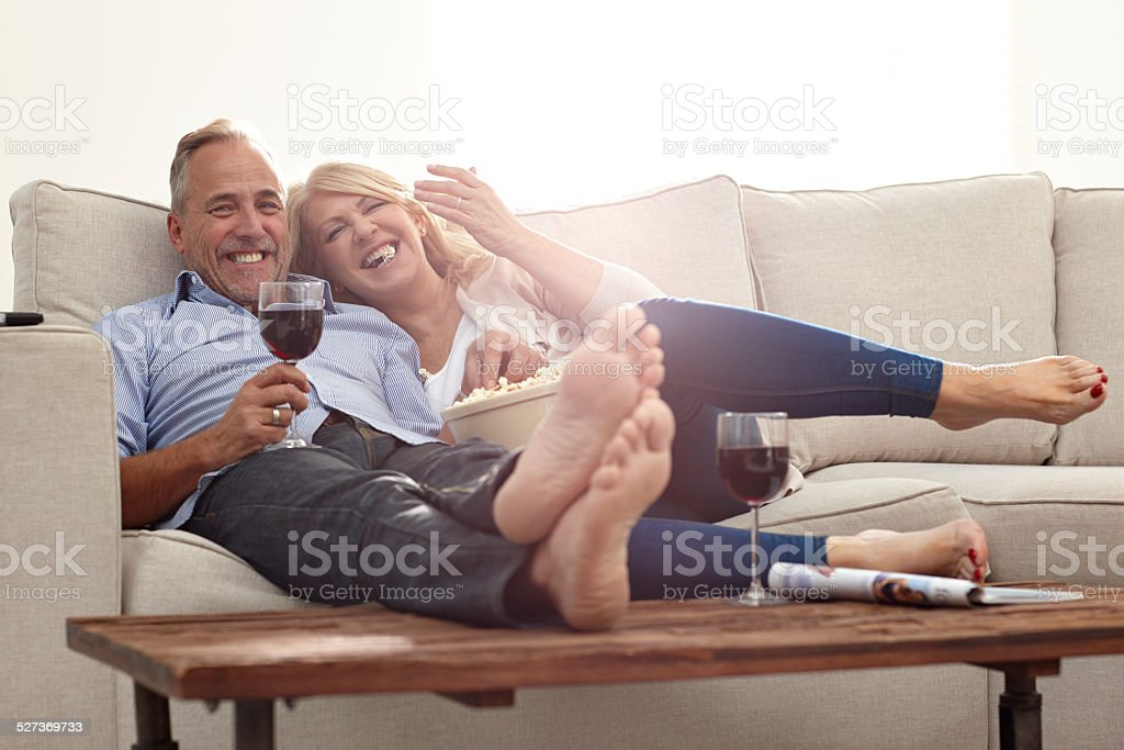 Mature couple enjoying watching movie at home stock photo