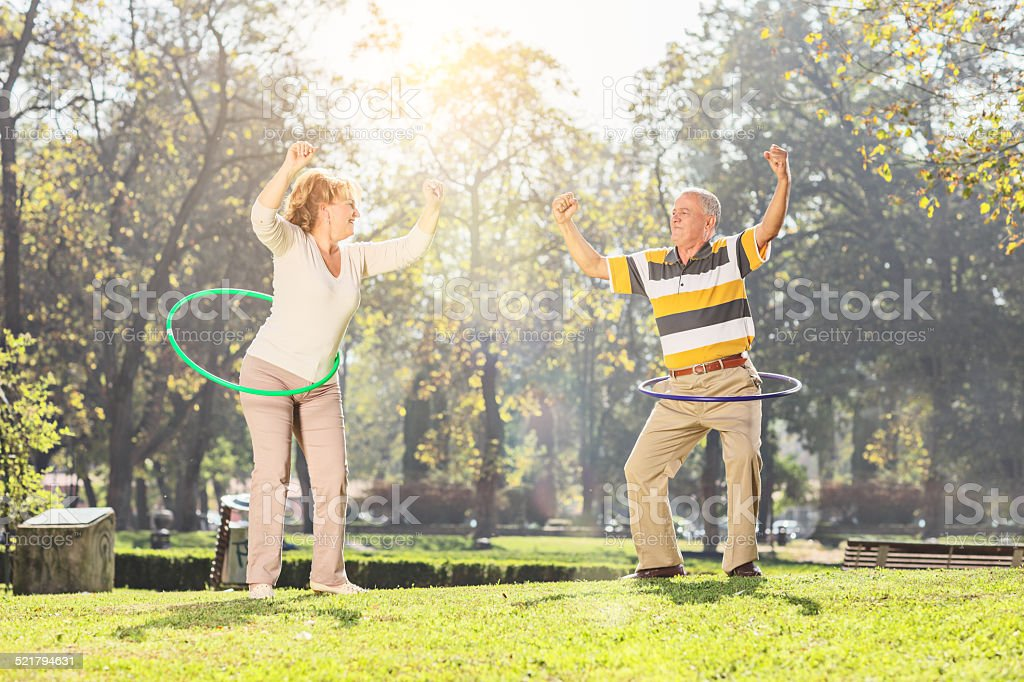 Mature couple exercising with hula hoops in park stock photo