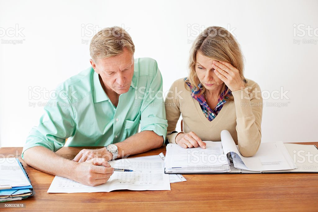 Mature couple going through monthly expenses bills stock photo