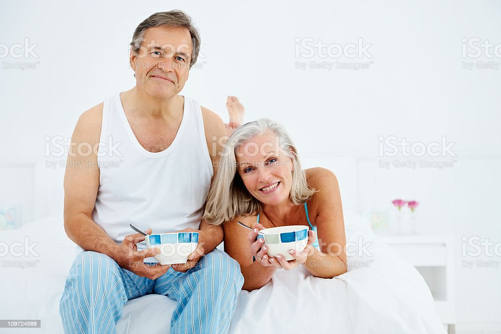 Mature couple having a healthy breakfast in bed royalty-free stock photo