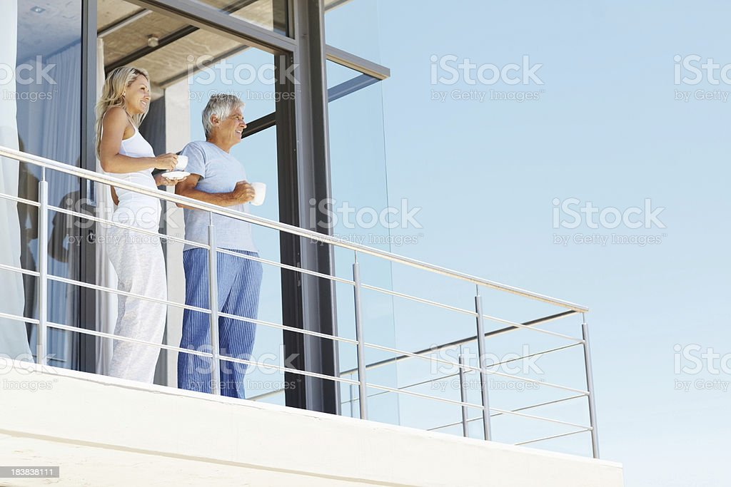 Mature couple having coffee at the balcony stock photo