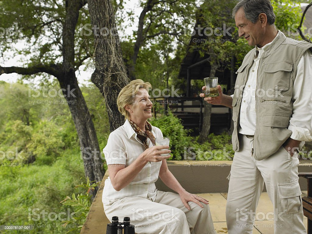 Mature couple having drinks on terrace at lodge, smiling royalty-free stock photo