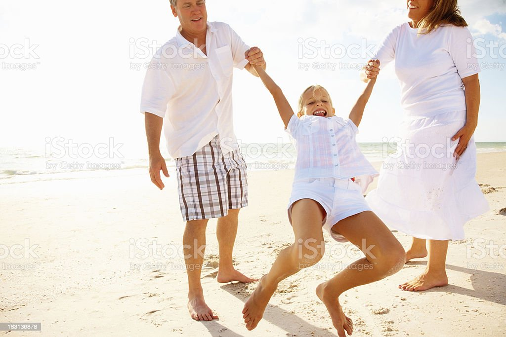 Mature couple having fun with their daughter on beach royalty-free stock photo