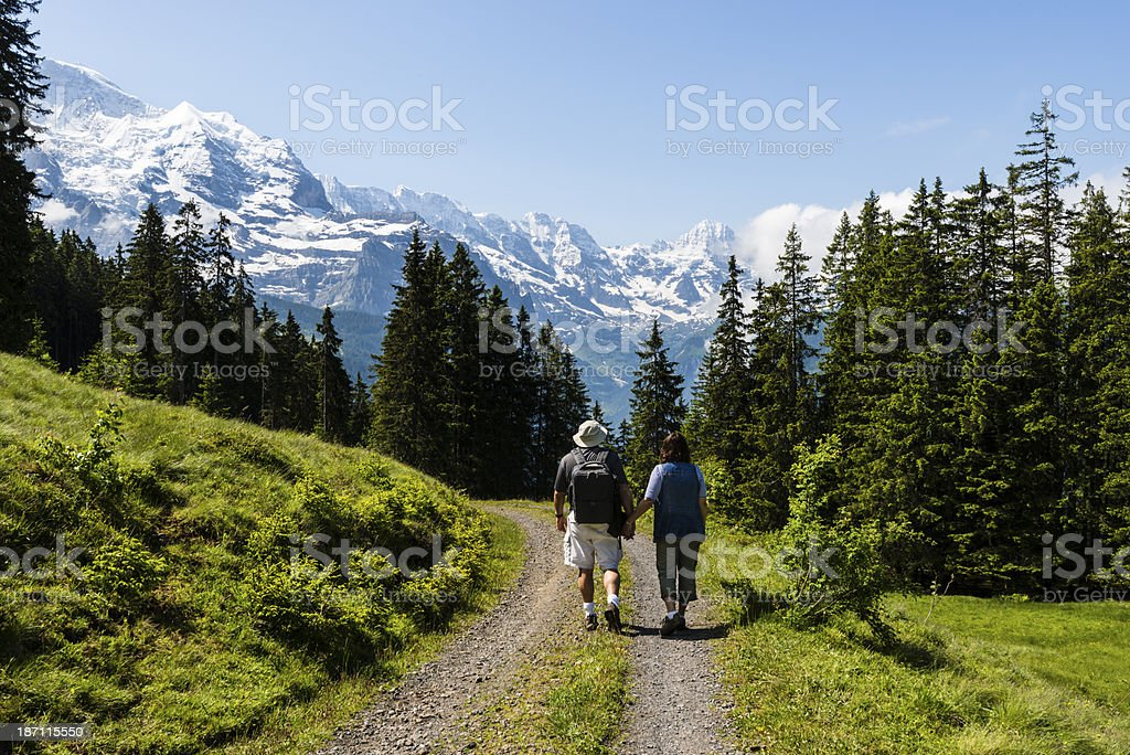 Mature couple hiking down a trail with beautiful mountain views.-XXXL royalty-free stock photo