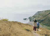 Mature couple hiking down bluff towards beach