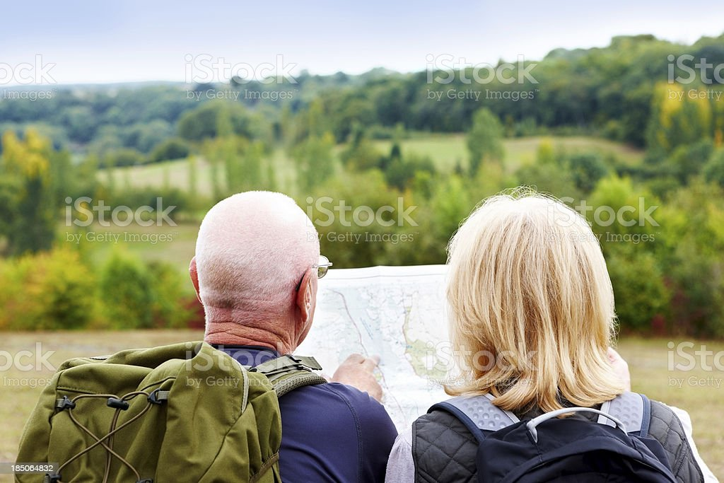 Mature couple hiking looking at map for directions royalty-free stock photo